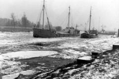 Schwarzenhütten Kümos im Eis warten auf einen Liegeplatz an der Pier